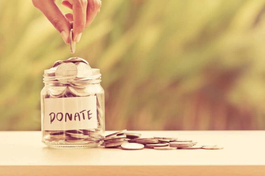 Ein Spendenglas steht auf einem Tisch und eine Münze wird hinein gegeben.