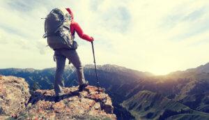 Wanderer steht oben auf einem Berg und blickt in die Ferne.