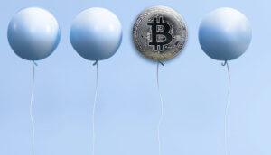 Vier Luftballons, der dritte von links mit einem Bitcoin-Symbol