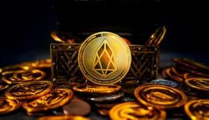 Man sieht eine Münze der Kryptowährung EOS in hellem Licht erstrahlen