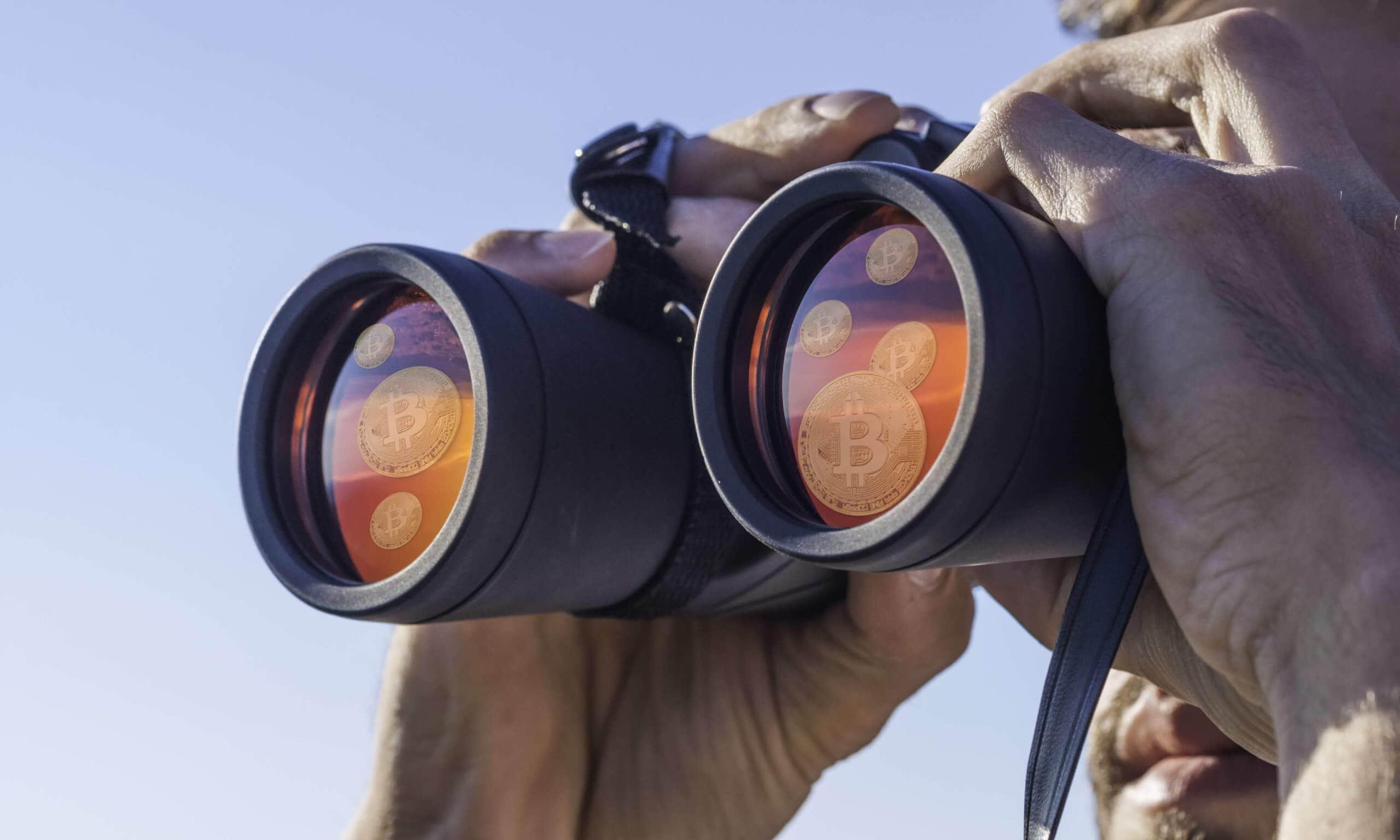 Ein Mensch blickt mit einem Fernglas in die Ferne, auf den Gläsern sieht man Bitcoin Münzen