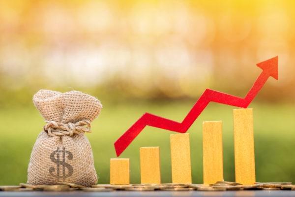 Geldsack mit US-Dollarzeichen sowie Balkendiagramm verdeutlichen einen Wachstumstrend.