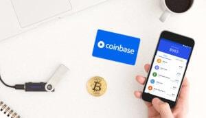 Man sieht ein Smartphone mit der Coinbase App, eine Bitcoin-Münze sowie ein HArdware Wallet auf einem Tisch liegen.