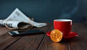 bitcoin-münze-vor-einer-kaffeetasse-auf-einem-holztisch-mit-zeitung-im-hintergrund