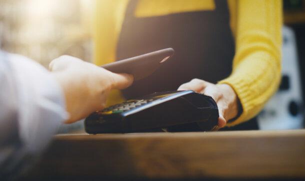 Im Geschäft wird mit einem Smartphone an der Ladenkasse bezahlt.