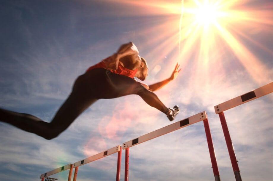 Ein Athlet überspringt eine Hürde