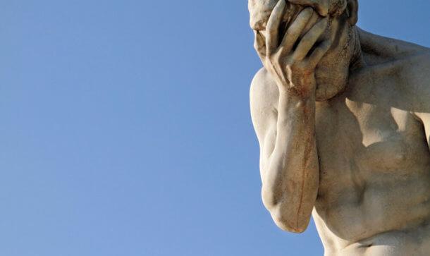 Eine Statur aus Stein verdeckt sich mit Hand das Gesicht.