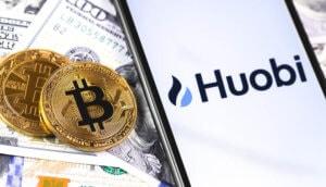 Auf einem Smartphone steht Huobi geschrieben und man sieht Geldscheine sowie Bitcoin-Münzen im Hintergrund.