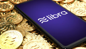 Libra-Logo auf Smartphone, das auf Goldmünzen mit Libra-Logo liegt