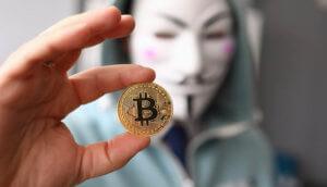 Symbollbild Binance-KYC-Leak: Mskierter Mann mit Bitcoin-Münze