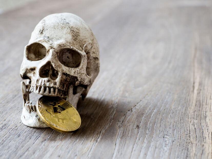 Totenschädel mit phyischer Bitcoin-Münze zwischen den Zähnen