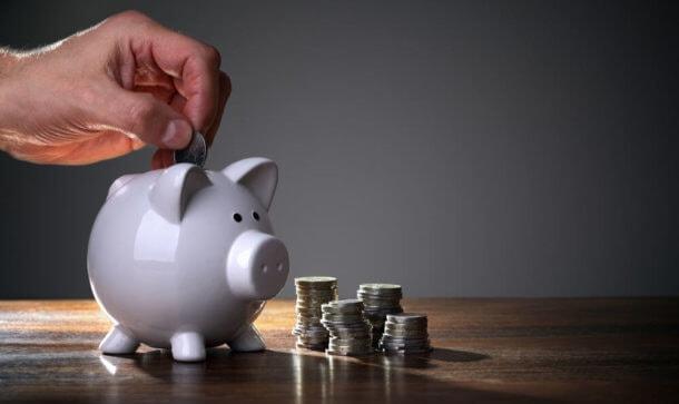 Ein weißes Sparschwein steht auf einem Tisch und eine Münze wird eingeworfen.