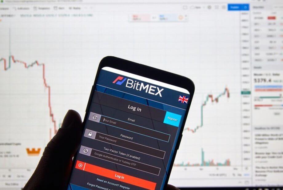 Smartphone mit App von BitMEX vor Desktop-Hintergrund mit Chart.