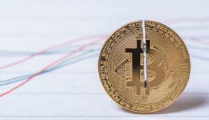 Eingeschnittene Bitcoin-Münze vor stilisiertem Chart