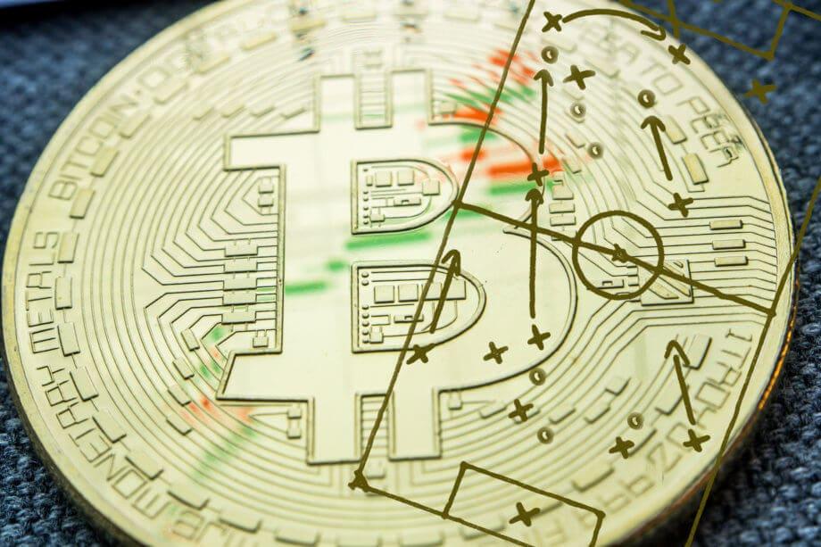 Bitcoin-Münze auf der ein Fußballspielfeld abgebildet ist