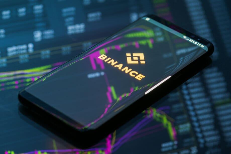 Smartphone, das das Logo von Binance zeigt, liegt auf einem gläsernen Grund, auf dem sich eine Chart spiegelt.