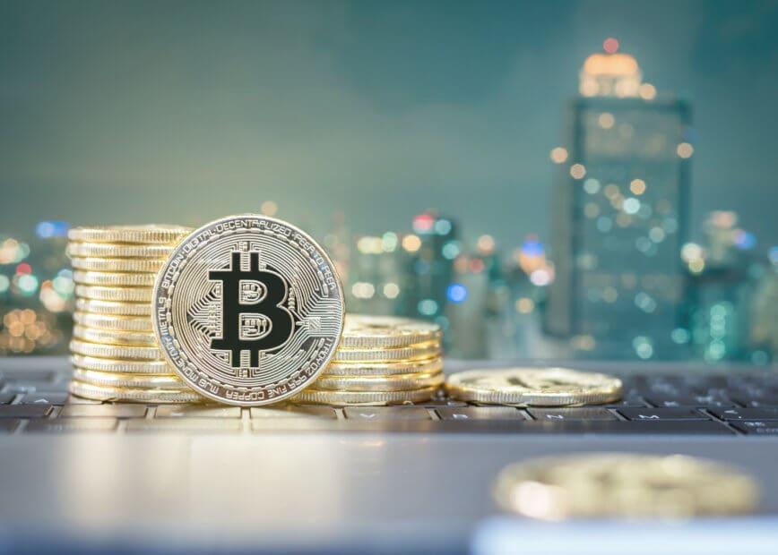 Eine aufgerichtete Bitcoin-Münze steht vor einem Stapel Bitcoin-Münzen, die vor einer Skyline liegend