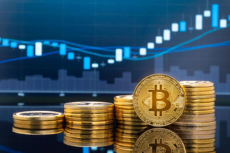 Eine aufgerichtete Bitcoin-Münze steht vor einigen aufgetürmten Bitcoin-Stapeln vor einer Chart.