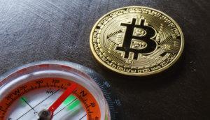 Bitcoin-Münze liegt neben einem Kompass auf einem Holztisch.