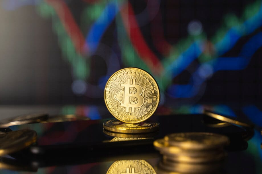 Bitcoin-Münze steht aufgerichtet auf einem Stapel Bitcoin-Münzen vor einer Chart.