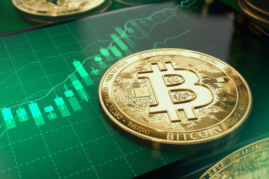 Bitcoin-Münze liegt auf einem Smartphone, das eine Chart mit grünen Kerzen abbildet.