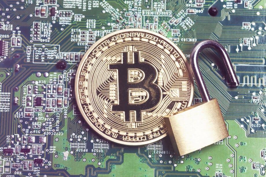 Eine Bitcoin-Münze auf einer Platine, daneben ein geöffnetes Schloss.