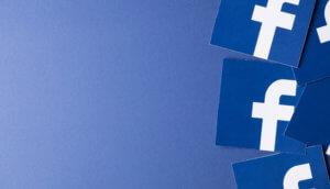 Flyer mit dem Facebook-Logo liegen verstreut vor einem blauen Hintergrund.