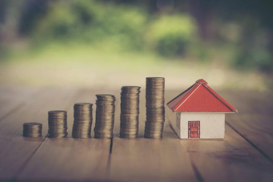 Gestapelte Münzen und Miniaturhaus sollen Sparen verdeutlichen
