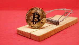 Eine Krypto-Münze, in dem Fall Bitcoin, in einer Mausefalle.