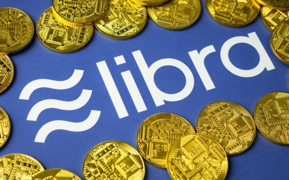 Libra-Münzen liegen auf einem blauen Hintergrund, der das Logo von Libra zeigt.