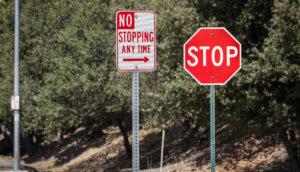Ein Stoppschild und ein dem wiedersprechendes das Stoppen verbietendes Schild direkt nebeneinander