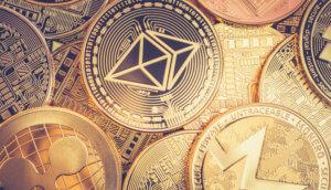 münzen der altcoins ether, xrp und monero liegen gestapelt