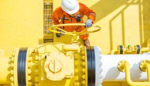 Arbeiter befindet sich auf gelber Bohrinsel für Öl und dreht an einem Ventil.