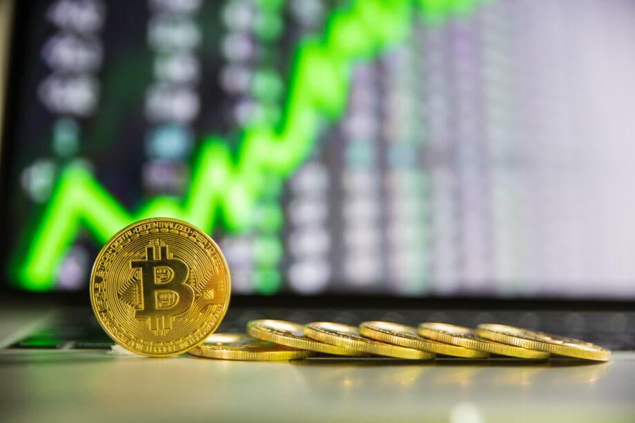 bitcoin-münze steht aufgerichtet neben liegenden bitcoin-münzen vor einer chart, die eine grüne kurve zeigt