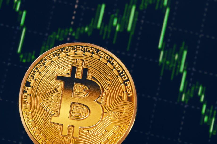 bitcoin-münze vor einer chart mit grünen kerzen