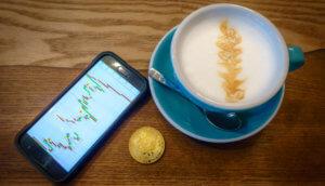 Smartphone das Charts zeigt, neben einer goldenen Bitcoin-Münze und einer Kaffeetasse mit Latteart auf einem braunen Holztisch