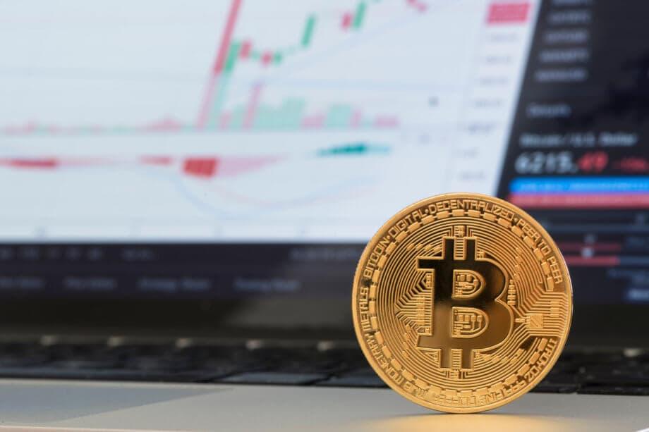 Eine stehende Bitcoin-Münze vor einer Analyse.