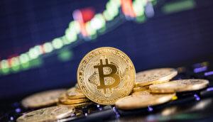 Goldene Bitcoin Münzen vor Charthintergrund
