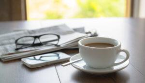Tasse Kaffe auf dem Tisch mit einem Fenster im Hintergrund. Neben der Tase ein Smartphone und eine Zeitung, auf der eine zugeklappte Brille liegt