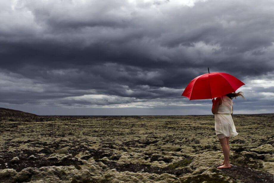 Frau mit rotem Regenschirm, die sich einem aufziehendem Sturm entgegenstellt