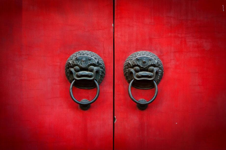 rote tür mit zwei china drachen als türgriffe, an denen jeweils ein ring hängt. man sieht in der mitte der beiden türhälften einen schwarzen spalt