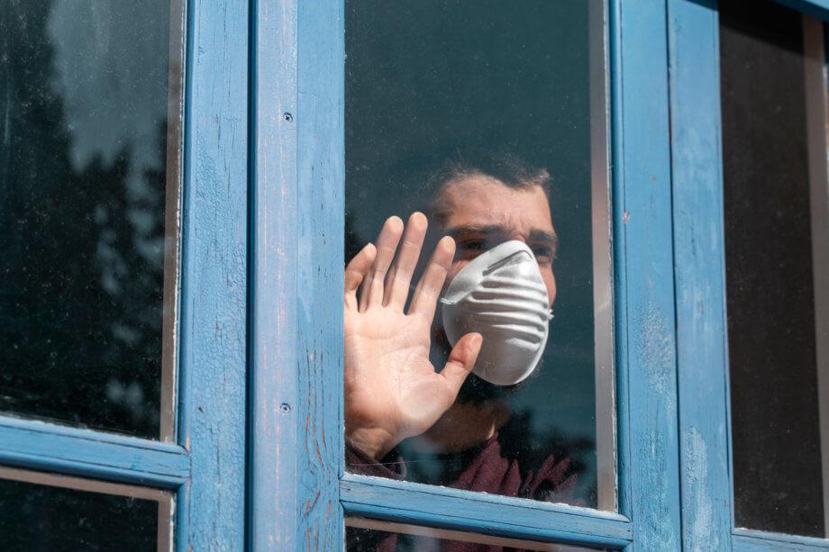 Sehnsuchtsvoll aus dem Fenster blickender Mann mit Mundschutz