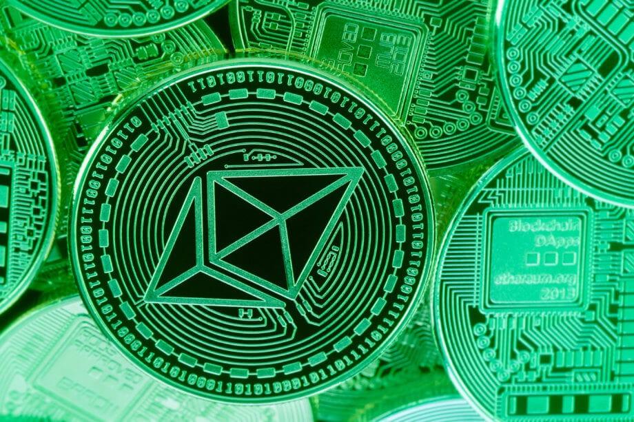 ethereum münze vor grünem hintergrund mit mehreren ether münzen