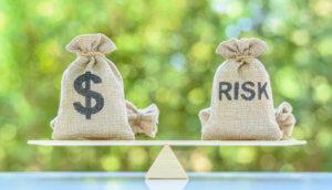 Balance zwischen Sack mit Dollarzeichen und Sack, auf dem Risk steht