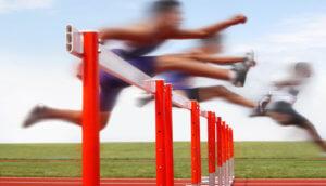 Läufer springen über rote Hürden