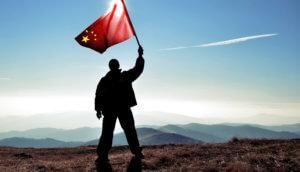 Mann steht auf Berg und hält chinesische Flagge hoch als Zeichen für den Start von CBDC