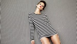 Model lehnt an schwarz weiß gestreifter Wand