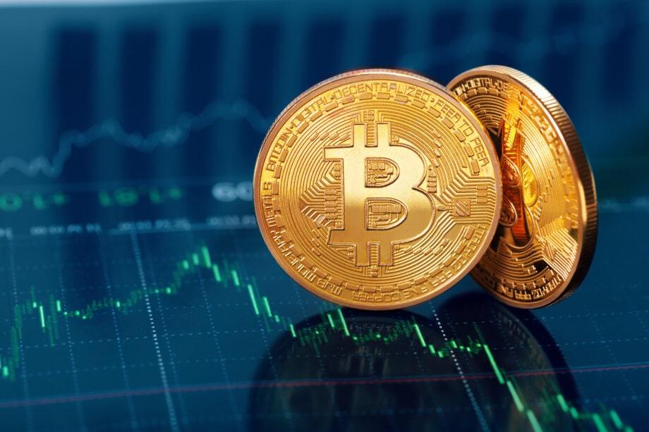 Zwei Goldene Bitcoin Münze auf Trendlinien im Hintergrund