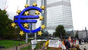 Eurozeichen im Vordergrund und im Hintergrund ein Frankfurter Bankgebäude