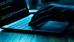 Hacker sitzt vor einem Laptop und tippt